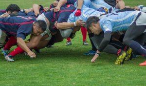 Ein Rugby-Team beim Scrum auf dem Feld